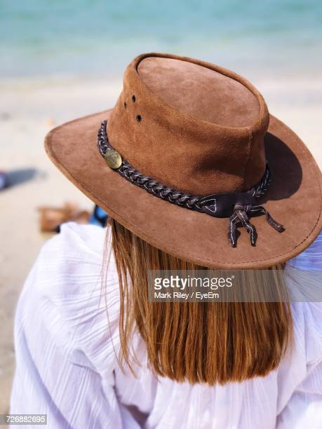 Rear View Of Woman With Long Brown Hair Wearing Hat At Beach