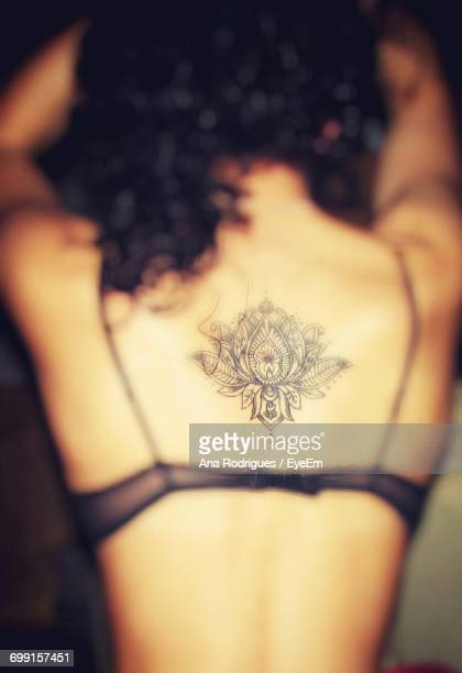 Rear View Of Woman With Lotus Tattoo On Back