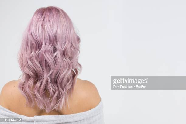 rear view of woman with purple hair standing against white background - mid length hair stock pictures, royalty-free photos & images