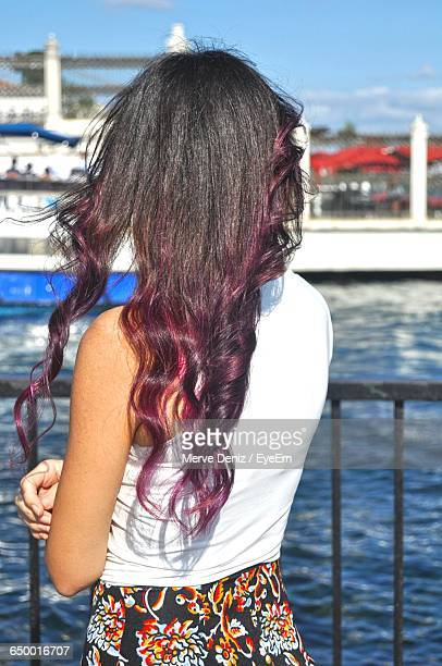 rear view of woman with purple hair standing in pier during sunny day - purple hair stock photos and pictures