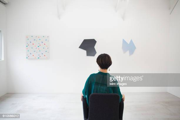 Rear view of woman with short black hair wearing green shirt sitting in art gallery, looking at modern paintings.