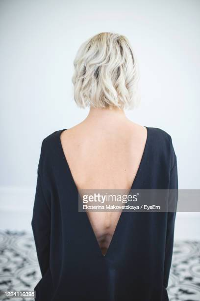 rear view of woman with short hair standing against white background - backless stock pictures, royalty-free photos & images