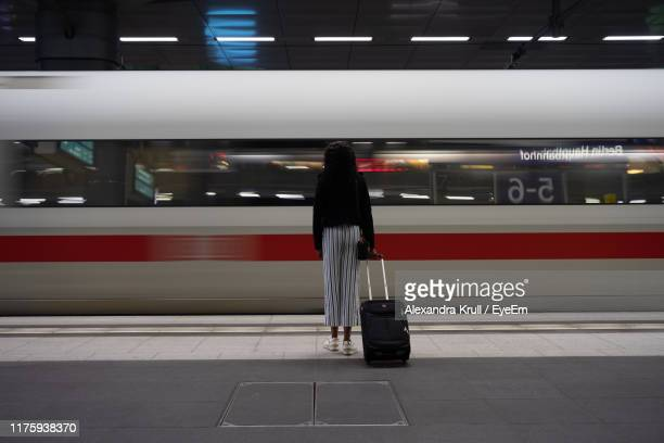 rear view of woman with suitcase by train at railroad station platform - waiting stock pictures, royalty-free photos & images