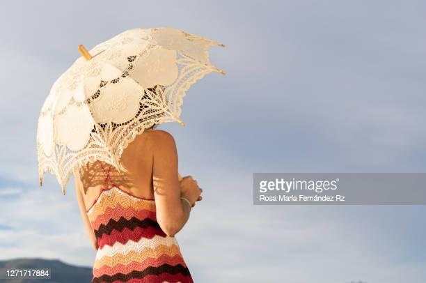 rear view of woman with sunshade looking the landscape against sky - plan moyen angle de prise de vue photos et images de collection