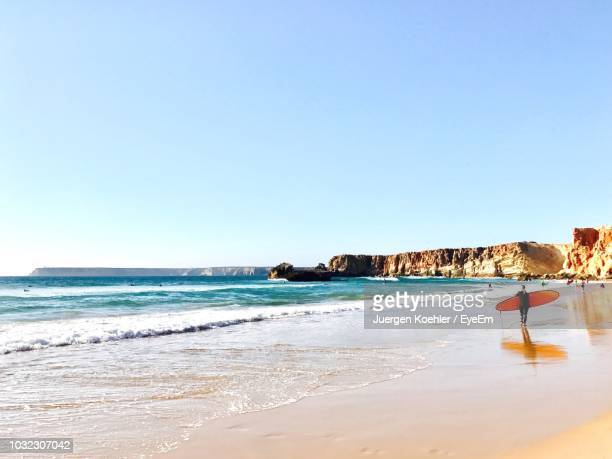 rear view of woman with surfboard on beach - sagres stock pictures, royalty-free photos & images