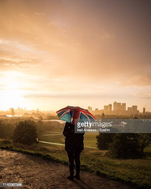 rear view of woman with umbrella standing on field against cloudy sky during sunset - sunlight stock pictures, royalty-free photos & images