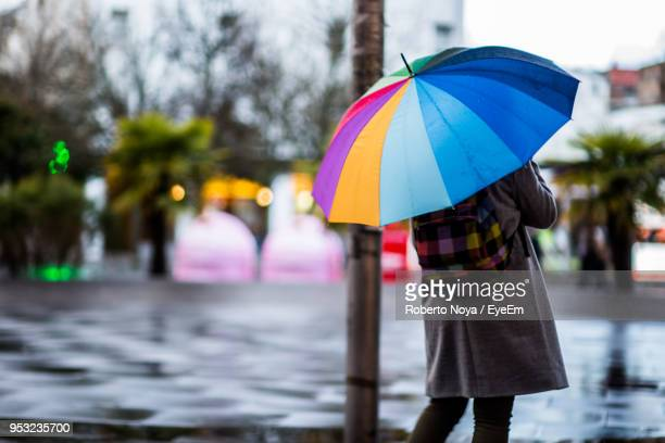 Rear View Of Woman With Umbrella Standing On Road