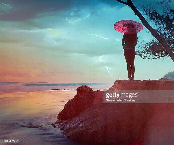 Rear View Of Woman With Umbrella Standing On Rock At Beach Against Sky During Sunset