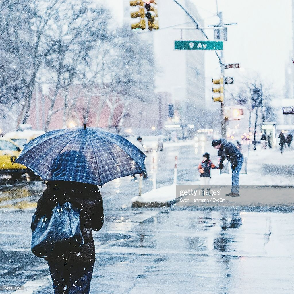 Rear View Of Woman With Umbrella Walking On Street During Snowfall