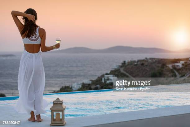 rear view of woman with wineglass standing at poolside against sea during sunset - ver a hora stockfoto's en -beelden