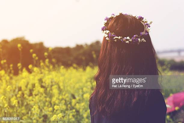 Rear View Of Woman With Wreath On Head Against Field