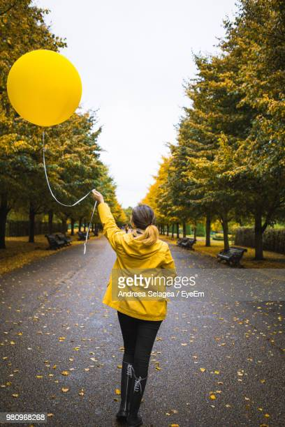 Rear View Of Woman With Yellow Helium Balloon Walking On Road At Park During Autumn