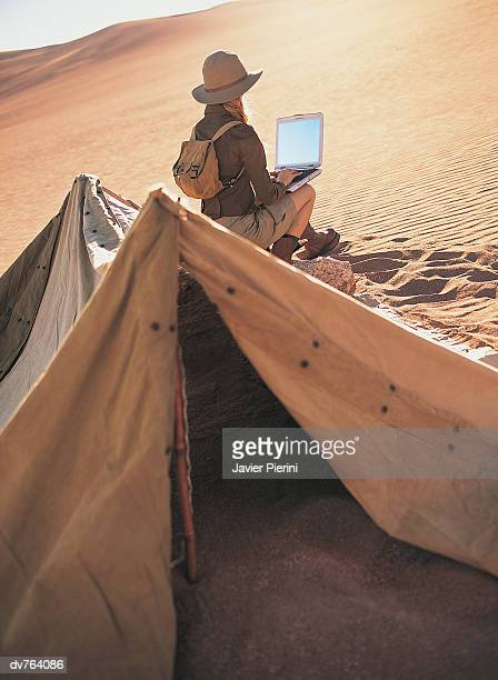 Rear View of Woman Working on a Laptop in the Desert