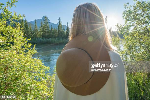 Rear view of woman wrapped in blanket looking at view