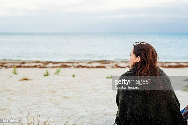 Rear view of woman wrapped in blanket sitting on beach