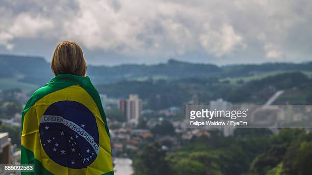 Rear View Of Woman Wrapped In Brazilian Flag Against Sky