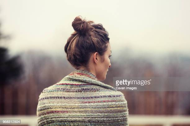 rear view of woman wrapped in shawl looking away - shawl stock pictures, royalty-free photos & images