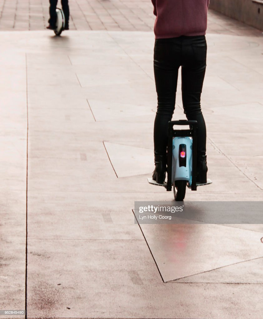 Rear view of woman's legs on electric unicycle riding along sidewalk : Stock Photo