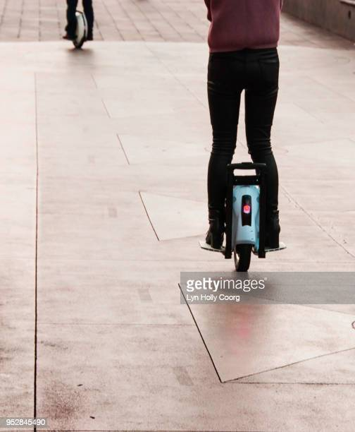 rear view of woman's legs on electric unicycle riding along sidewalk - lyn holly coorg stock pictures, royalty-free photos & images