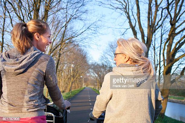 Rear view of women face to face cycling on tree lined road