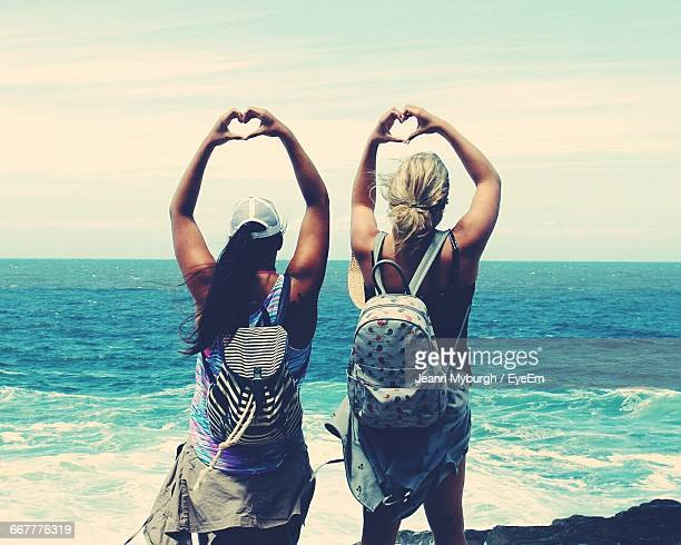 Rear View Of Women Forming Heart Shapes With Hand At Beach
