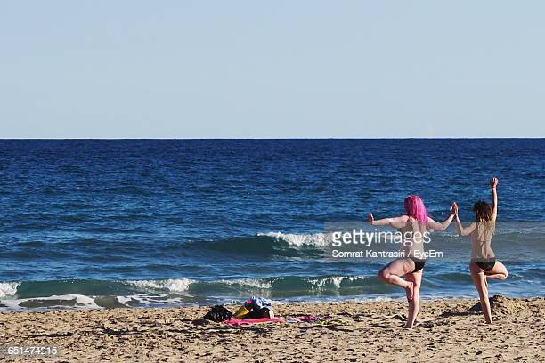 Rear View Of Women Holding Hands While Doing Yoga At Beach Against Clear Sky