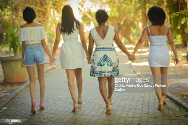 rear view of women holding hands while walking on footpath - mini jupe photos et images de collection