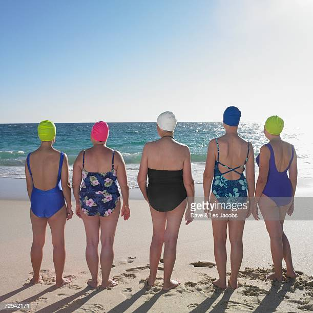 rear view of women in bathing suits at beach - sea swimming stock photos and pictures