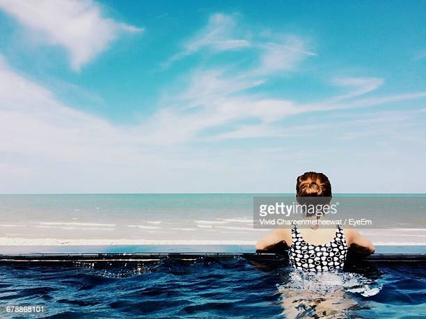 rear view of women in swimming pool next to beach against cloudy sky - 特定できない人物 ストックフォトと画像