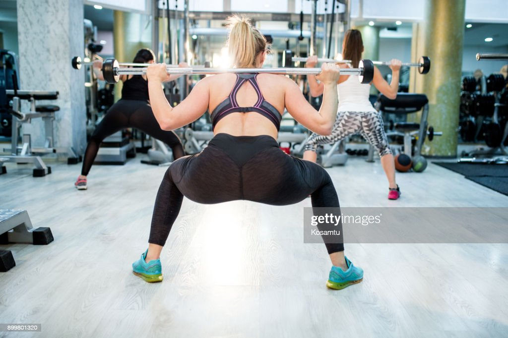 Rear View Of Women Lifting Weights And Doing Squats Stock