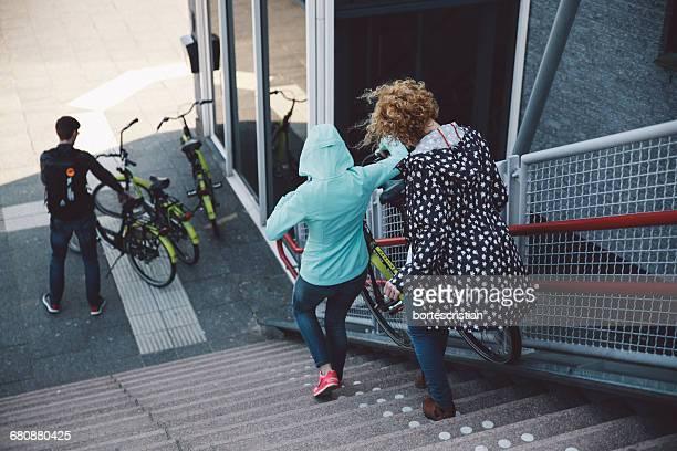 rear view of women moving down staircase - bortes stockfoto's en -beelden