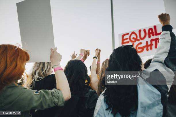 rear view of women protesting for equal rights against sky in summer - women politics stock pictures, royalty-free photos & images