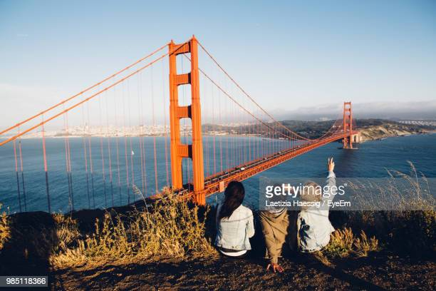 rear view of women sitting against golden gate bridge - north america stock pictures, royalty-free photos & images