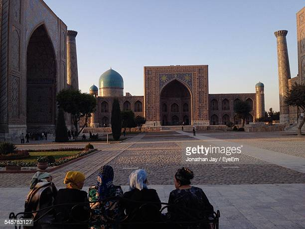 Rear View Of Women Sitting At Registan Square Against Clear Sky
