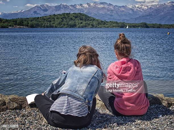 Rear View Of Women Sitting By Lakeshore