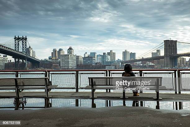 Rear View Of Women Sitting On Bench Against Brooklyn Bridge Over East River