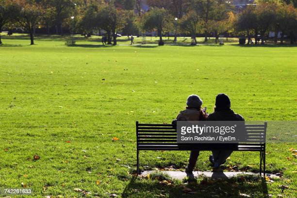 Rear View Of Women Sitting On Bench At Park