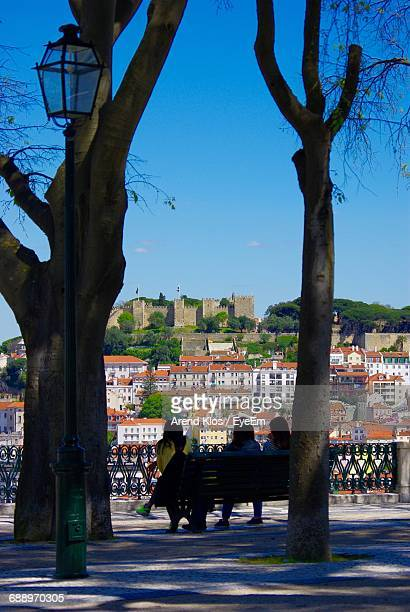Rear View Of Women Sitting On Bench While Looking At City Against Sky