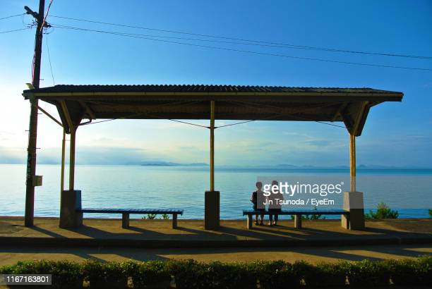 rear view of women sitting on bench while looking at sea against sky - matsuyama ehime stock pictures, royalty-free photos & images
