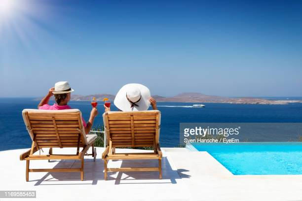 rear view of women sitting on chair by sea against sky - standing water stock pictures, royalty-free photos & images