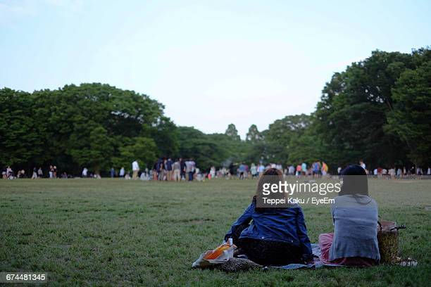 Rear View Of Women Sitting On Grass At Yoyogi Park Against Sky