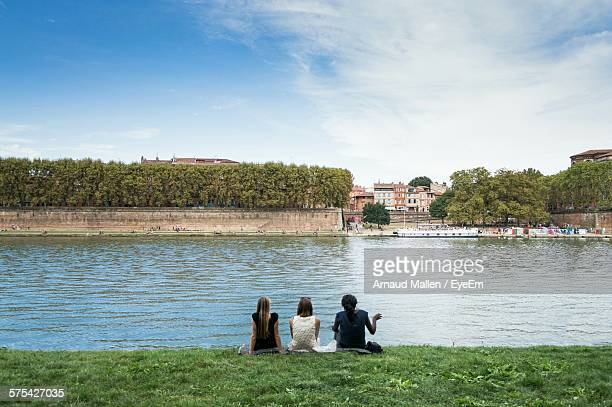 Rear View Of Women Sitting On Riverbank Against Sky