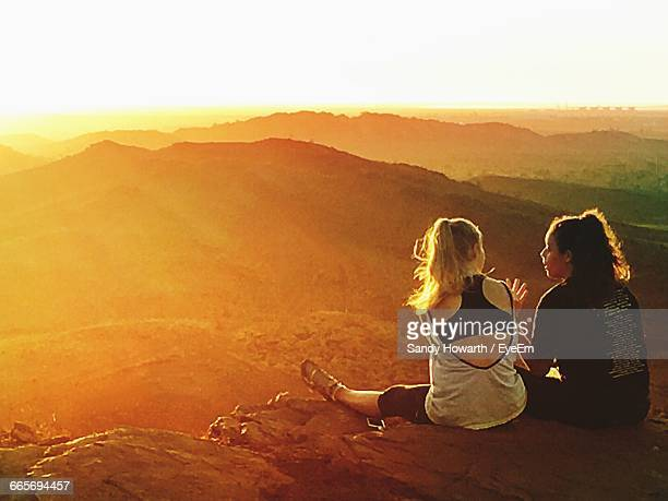 Rear View Of Women Sitting On Rock Against Sky During Sunset