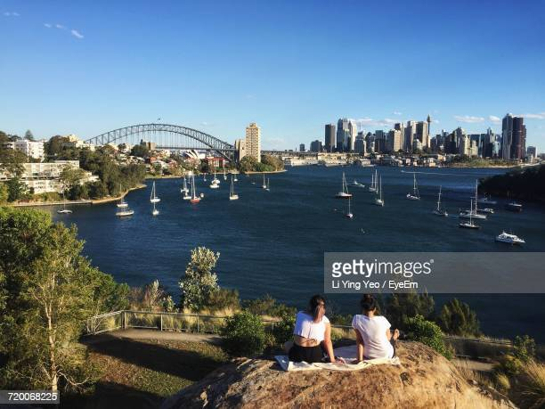 Rear View Of Women Sitting On Rock At Balls Head Reserve Against Sydney Harbor In City
