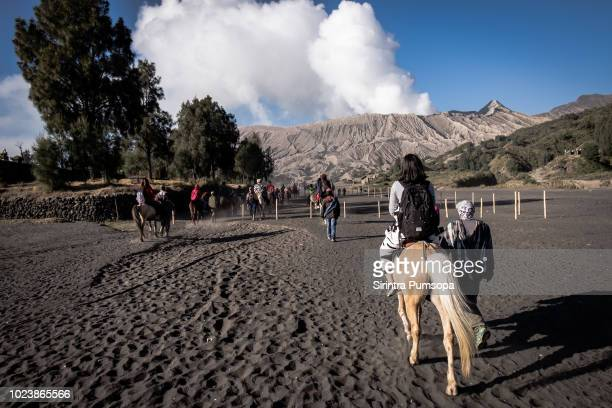 Rear View Of women tourists riding a horse to Bromo volcano mountain at Bromo Tengger Semeru National Park in East Java, Indonesia