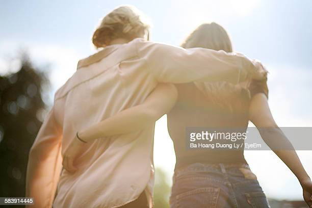rear view of women walking arm around outdoors - arm around stock pictures, royalty-free photos & images