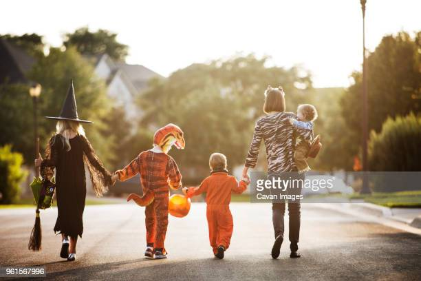 rear view of women with children dressed for halloween party walking on street - happy halloween stock photos and pictures