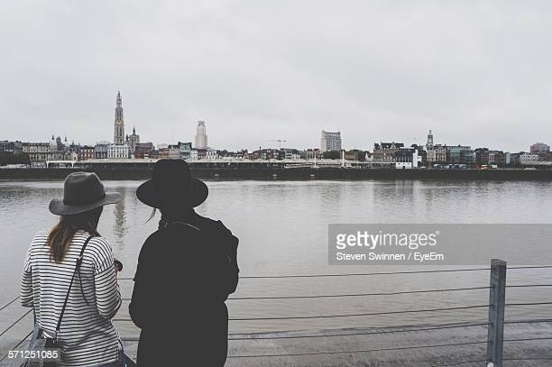 Rear View Of Women With Hats Standing By Fence In Front Of River Against Sky