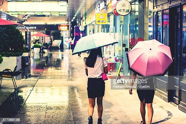 rear view of women with umbrella walking in sidewalk in city - parham emrouz stock pictures, royalty-free photos & images