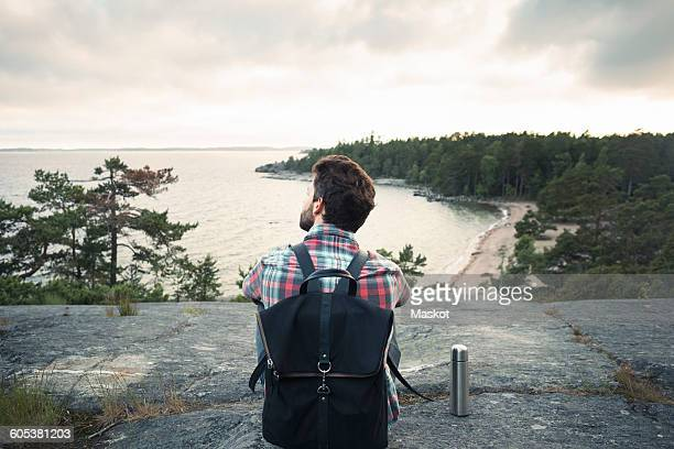 Rear view of wonderlust man sitting on rock at lakeshore